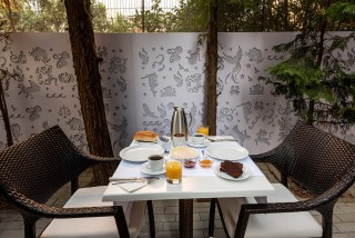 gallery galaxias hotel offers greek breakfast in a cozy outdoor environment surrounded by a garden