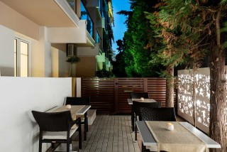 gallery galaxias hotel outdoor lounge area with many tables and chairs surrounded by a garden