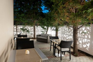 gallery galaxias hotel outdoor sitting areas with many chairs and tables next to a green garden